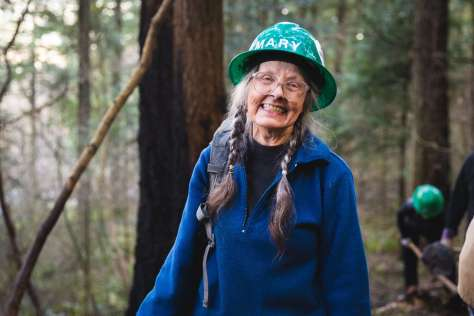 A woman in a green hard hat smiles for the camera.