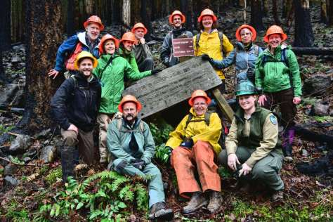 A dozen people in hard hats and rain gear cluster around a fallen over wood sign.