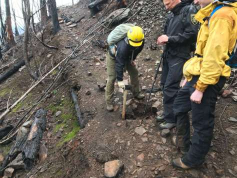 Two people look on while a third sticks an ax handle into a deep hole in the middle of a trail on a burnt-over slope.