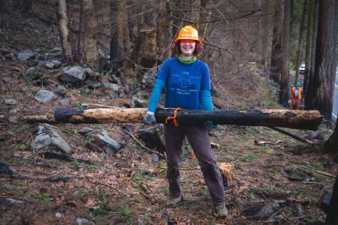 A woman wearing a hard hat carrying a burned log.