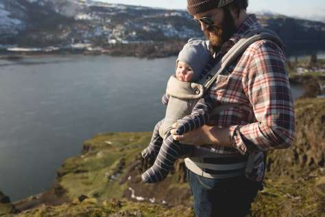 A man with a baby in a baby carrier on his chest standing on a cliff high above a wide river.