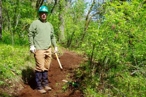 A trail worker in a green hard hat and wearing gaiters stands in the middle of a dirt trail holding the broken=off handle of a trail tool.