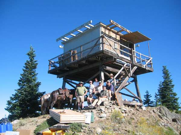 A group of people sit and stand on the ground with construction materials in front of a cabin on stilts.