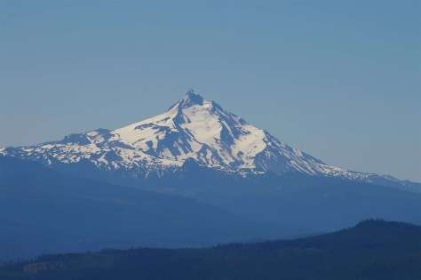 A snowy volcanic mountain with a sharp peak beyond ridgelines in the foreground.
