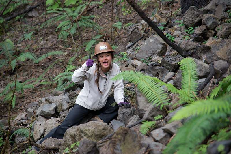 A hard-hatted woman on a rocky slope, giving a thumbs-up.