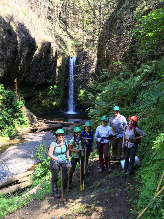 Six hard-hatted workers with tools in hand pose on a trail with a waterfall in the background.