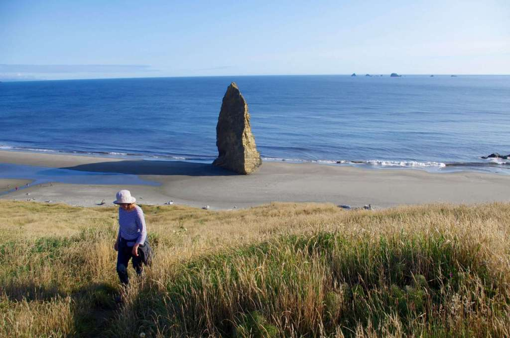 A woman walking across grassy dunes in the foreground, a tall sea stack casting a long shadow on a beach in the middle ground, and rocky islands in the ocean in the background.