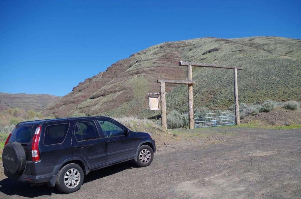 A car parked at a trailhead.