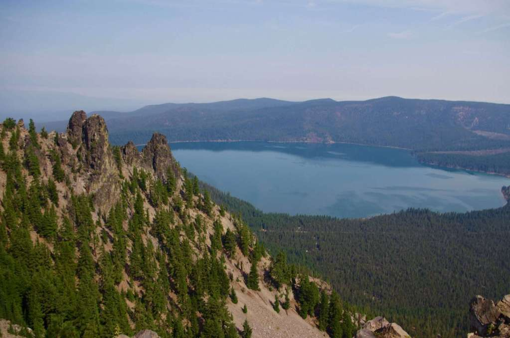 Rock formations on a steep slope, with a lake below.