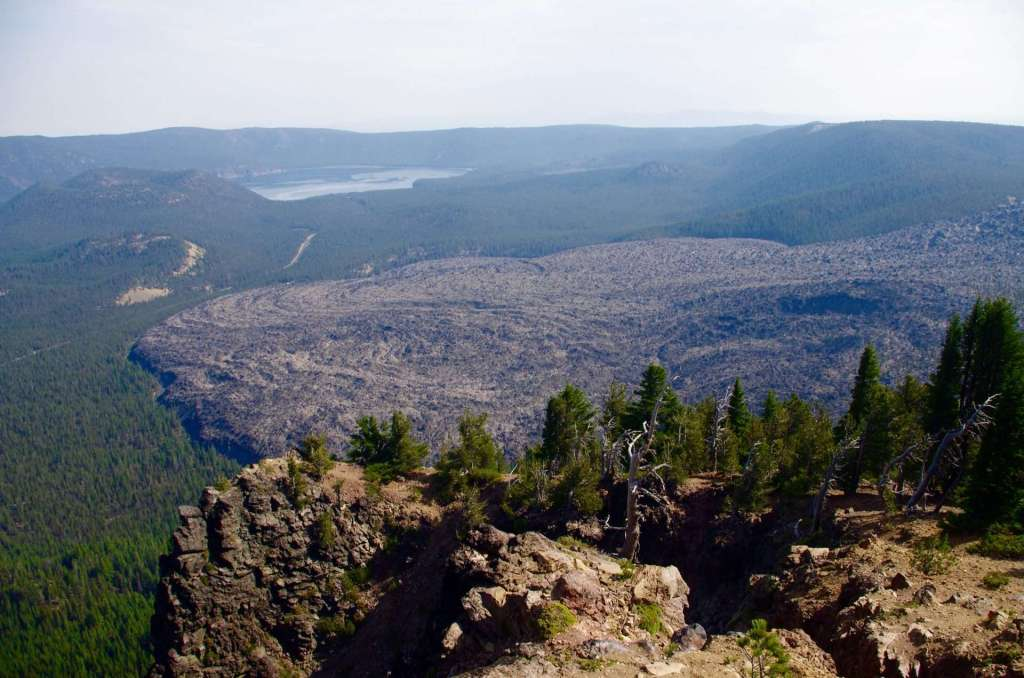 A cliff in the foreground, the grayish-black swirl of an immense lava flow far below, a lake beyond, and a caldera rim in the distance.