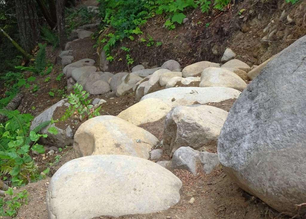 Alt Text: Dozens of boulders arranged in a curve descending a steep slope.