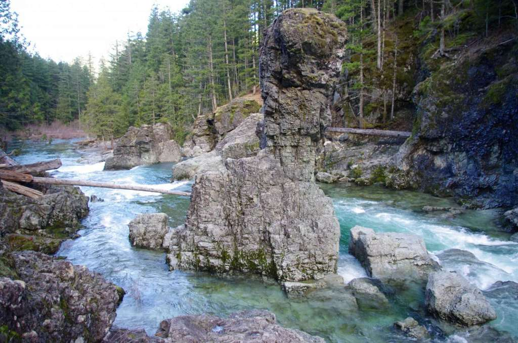 A rock pillar stands up from the middle of a greenish-blue river bordered by light grey rocks and dark green coniferous forest.