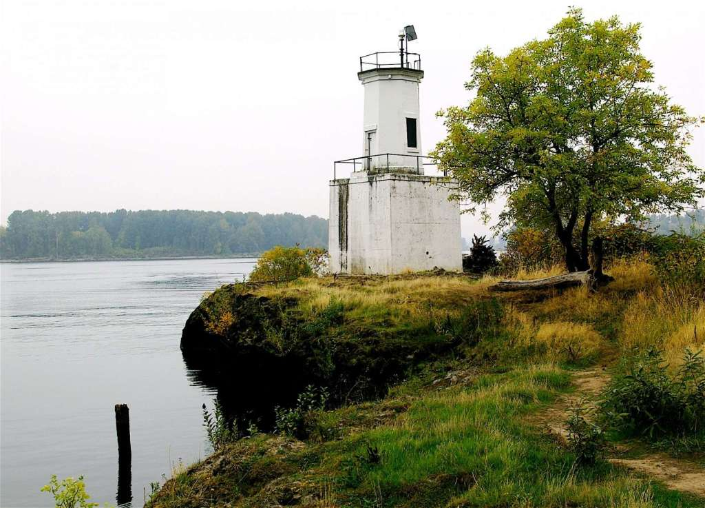A small lighthouse on a wide river.