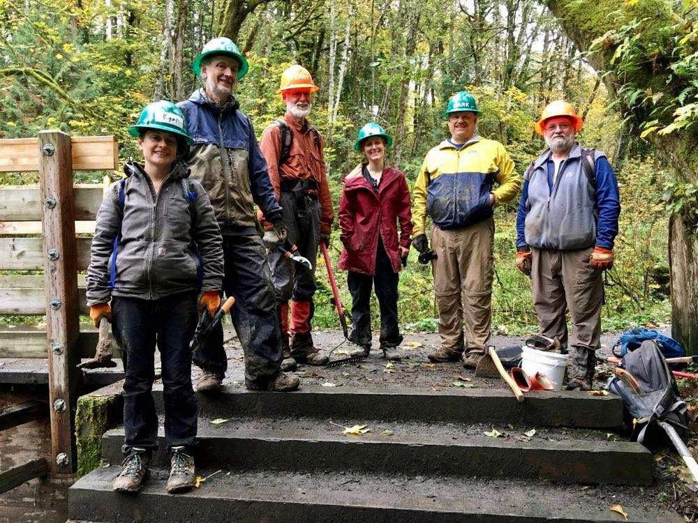 Six trail volunteers in hard hats posing above a short staircase on a trail in a wooded area.
