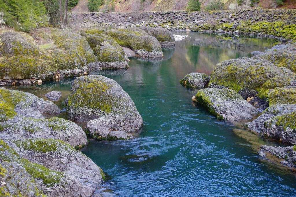 A clear blue river flows through an area of rounded boulders.