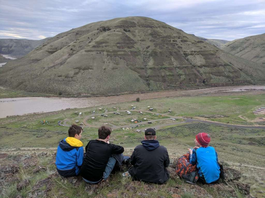 Four boys sitting on a hill overlooking a campground next to a muddy river, with a treeless slope across the river.