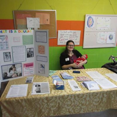 Certified Doula Shalynne Addison manning a doula information booth with baby