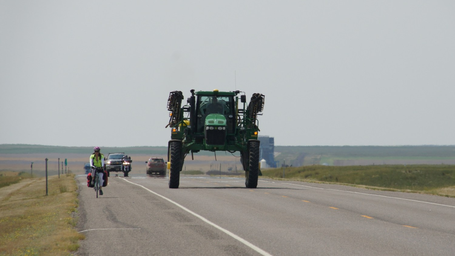 Chelsea and a giant piece of farm machinery share Highway 2 in northern Montana.