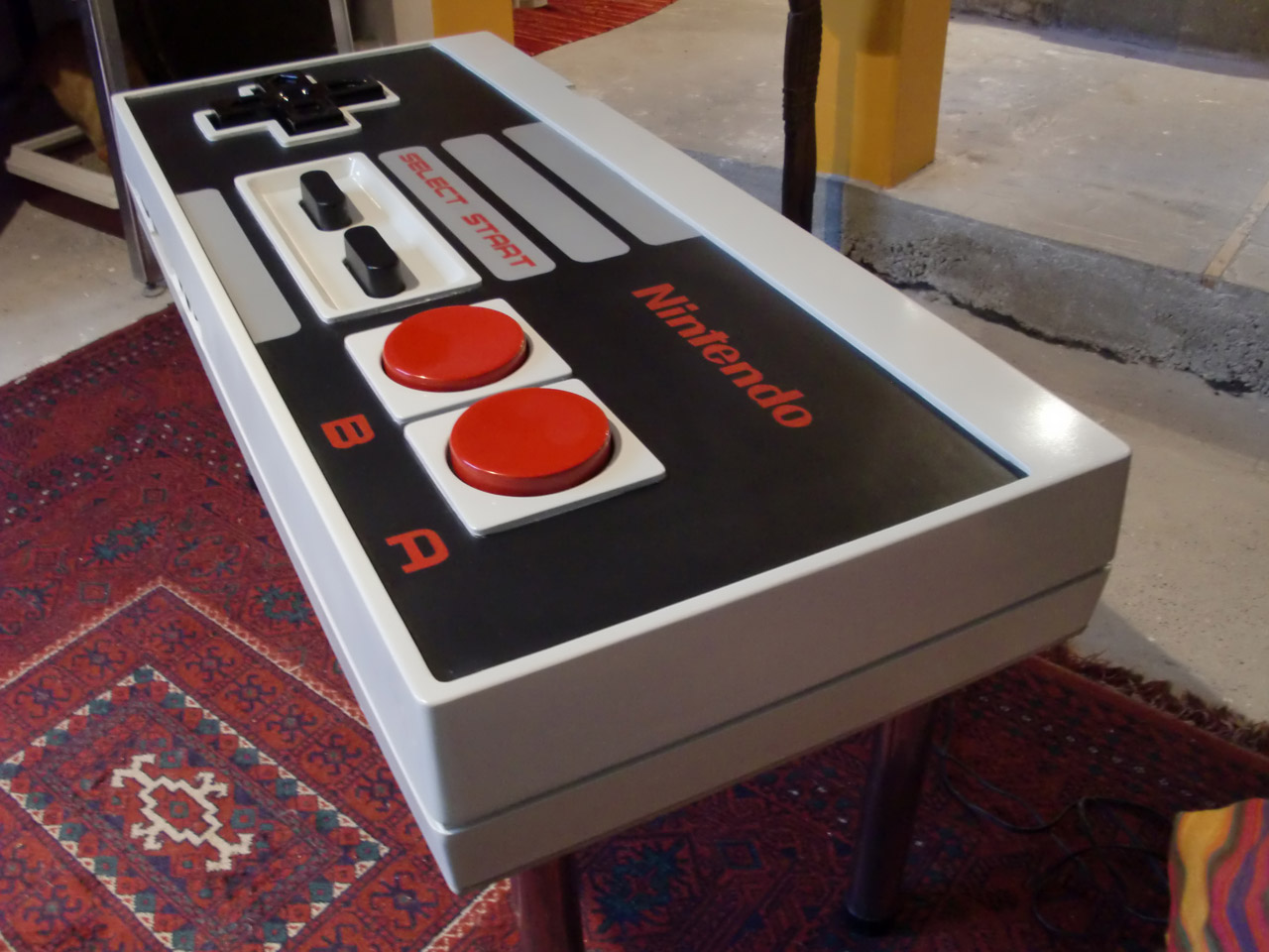Une Manette De SuperNes Gante Qui Sert De Table