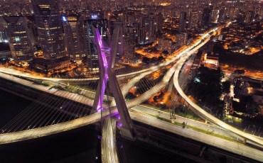 Imagem da Ponte Estaiada com luzes roxas sobre a marginal Pinheiros à noite.