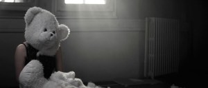 Woman Sitting In Derelict Room Surrounded By Wool With Teddy Bear Mask