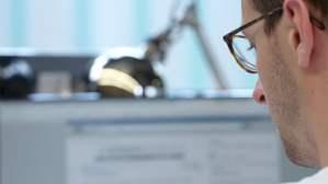 Man Sitting At Desk Coding
