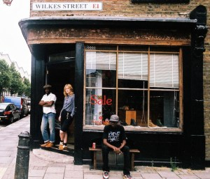 Professional Photography Black Man Sitting Outside Of Grenson Shoe Store Wearing Bathing Ape With Two People In Doorway In Brick Lane Wilkes Street