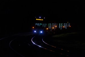 Professional Photography Tram Train At Night In Shadows With Bright Highlights Coming Around Bend In South Norwood London