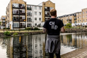 Professional Photography White Man Wearing Black Child.org T-Shirt And Grey Hoody Wrapped Around Waist Standing In Front Of River Canal With Buildings In Background