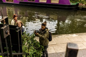 Professional Photography Black Woman In Khaki Jacket And Black Backpack Next To Canal River And Boats Filming With Camera In Little Venice Paddington London