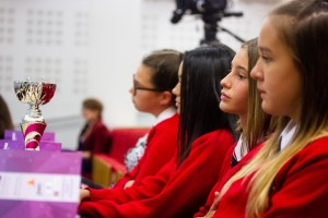 Professional Photography Four Female Students Wearing Red Sweatshirts Sitting Watching Event With Silver And Pink Trophy
