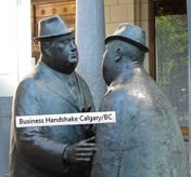 two men shake hands - bronze statues in Calagary/BC