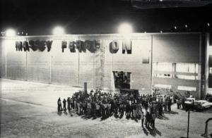 A foto mostra operários reunidos em frente à porta de entrada da fábrica. Sobre eles, holofotes iluminam a fachada da fábrica Massey Ferguson.
