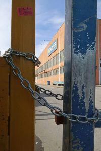 Foto de portão de entrada de empresa fechado com cadeado.