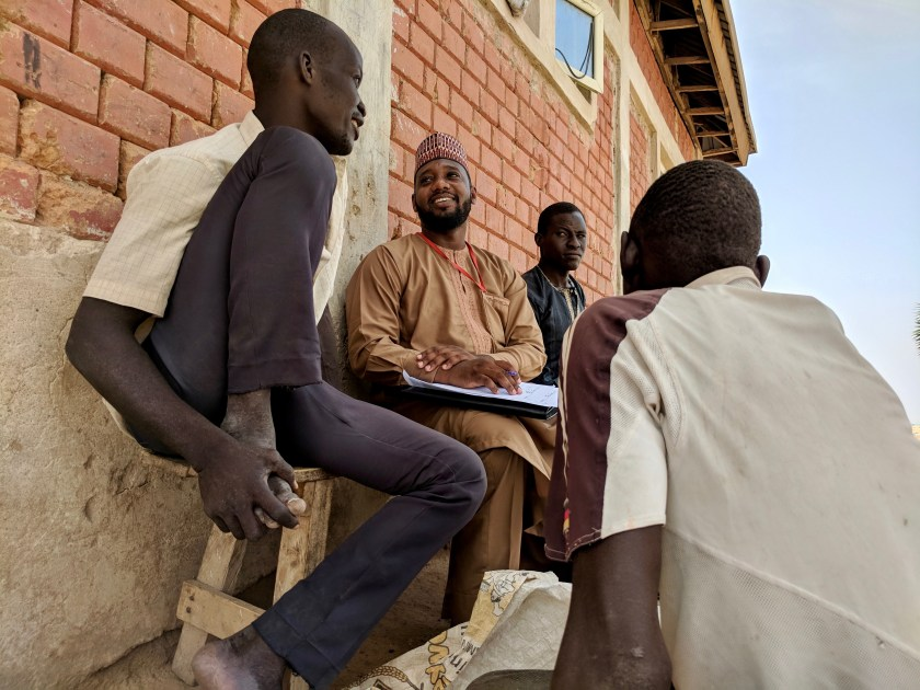 "Yahaya (center left) TWB Kanuri Team Leader conducts research on how well words like ""stress"" and ""abuse"" are understood in Kanuri and whether words like ""rape"" and ""mental health"" carry a stigma."