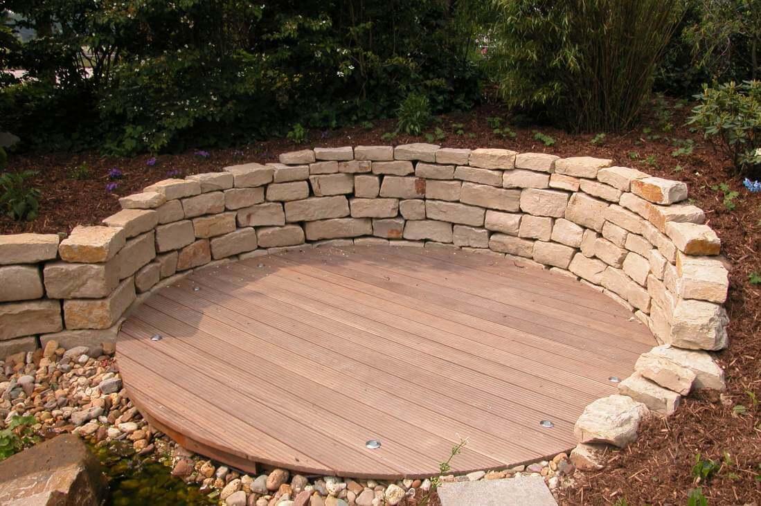 Sitzplatz aus Hartholz mit Natursteinmauer