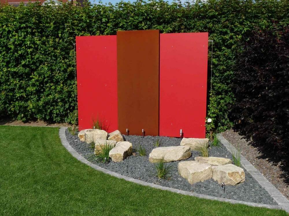 Eine Wasserwand aus Cortenstahl in Kombination mit roten Resopalplatten