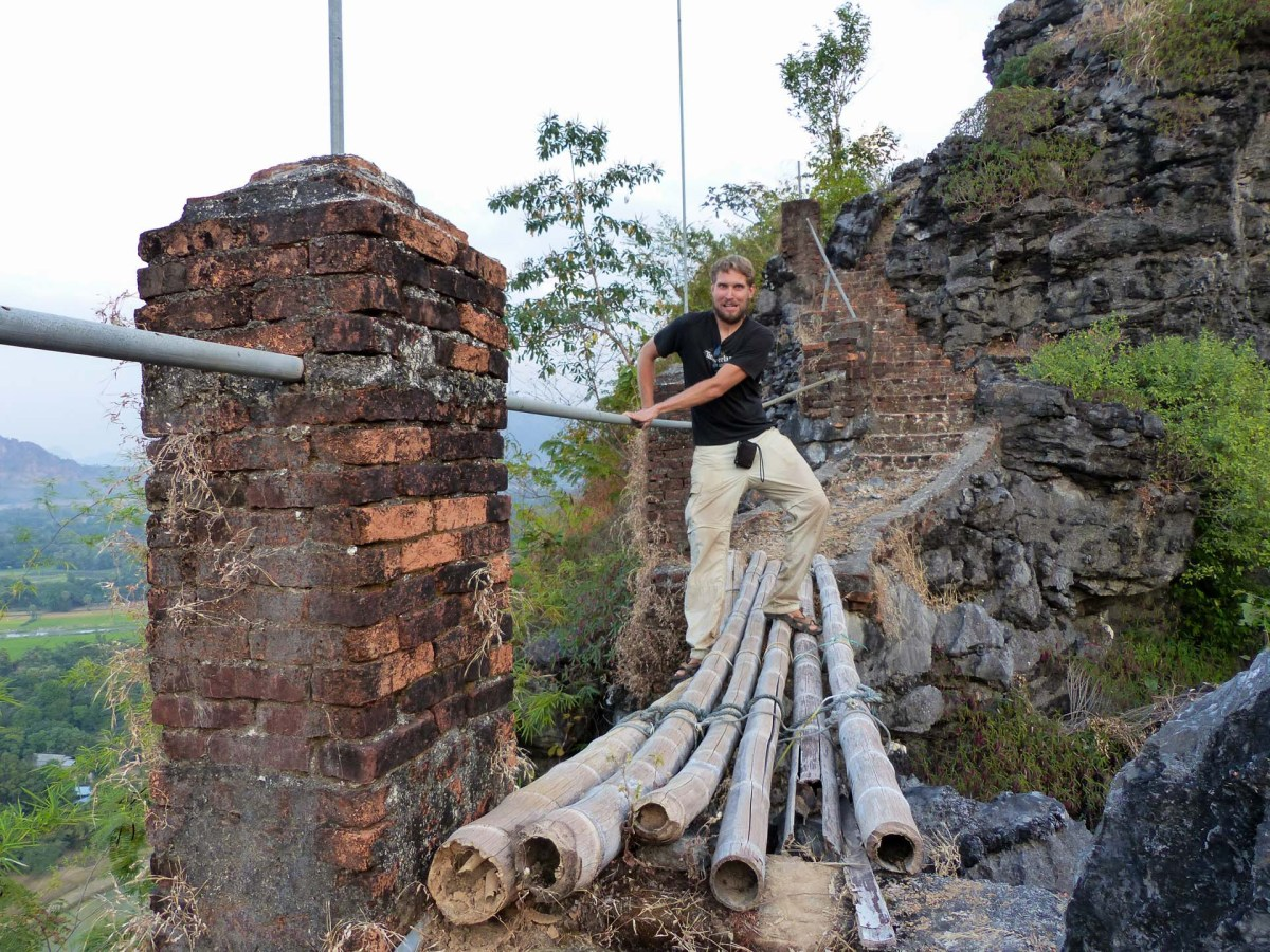Christian passing a broken bamboo bridge on the mountain top at Kawtka Taung Cave