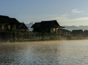 Mists lifting in front of stilt houses on Inle Lake