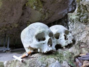 Tana Toraja - human skulls in ancient funeral caves with cigarette donation for the spirits Christian Jansen & Maria Düerkop