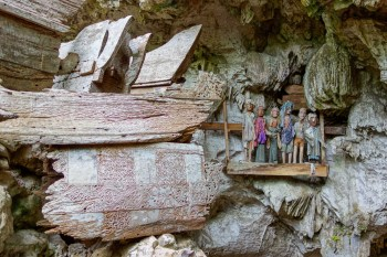 Tana Toraja - wooden figures and broken sarcophagus in ancient funeral caves Christian Jansen & Maria Düerkop