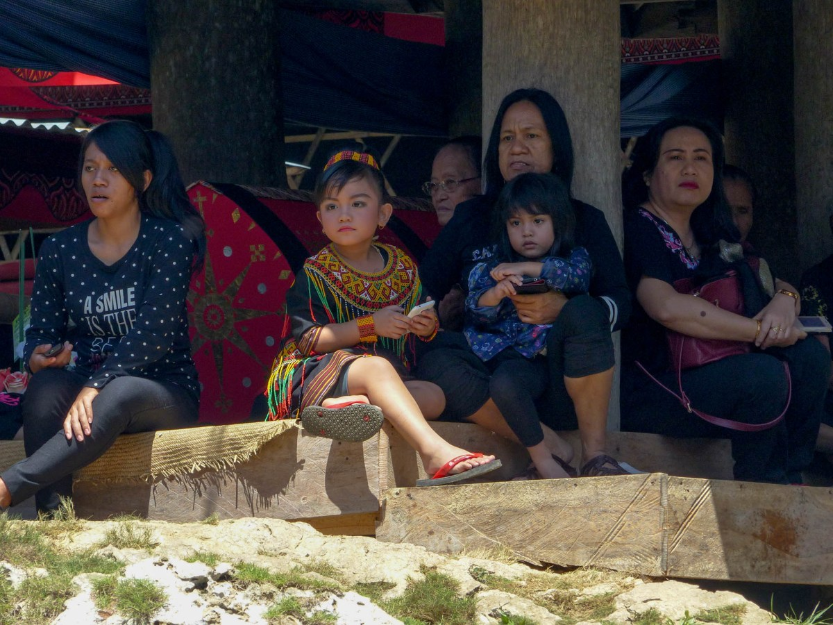 Tana Toraja Funeral Ceremony - grandchild of the deceased with cellphone Christian Jansen & Maria Düerkop