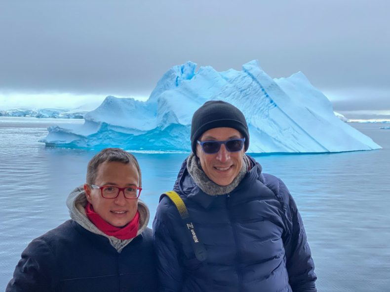 Rick and Andrea in front of an Iceberg on their Cruise to Antarctica