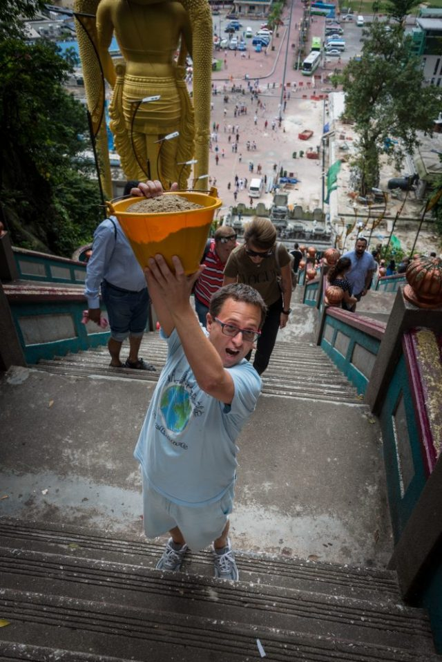 Rick helping the Locals Bring sand up the stairs at Batu Caves