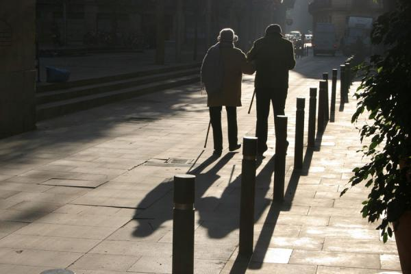 Image of Old couple walking the streets of Sant Pere with their shadows, Barcelona, Spain