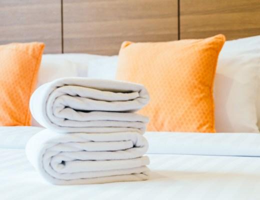 white bath towel on bed, orange pillow