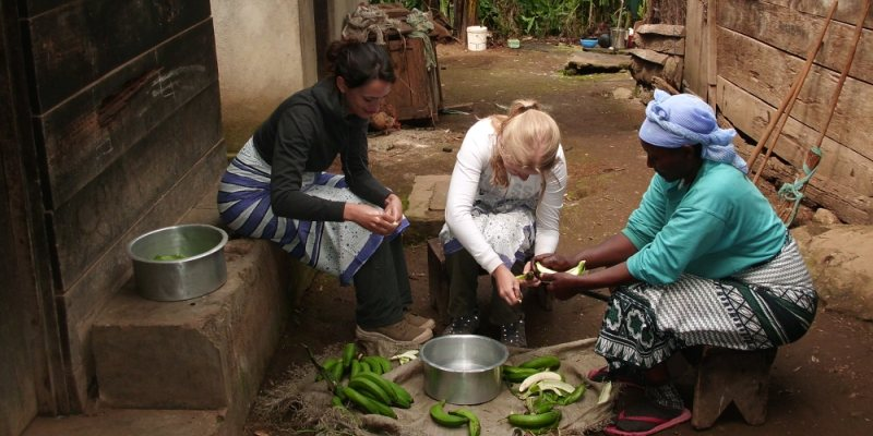 Guest in Machame with the host preparing banana for meals.JPG