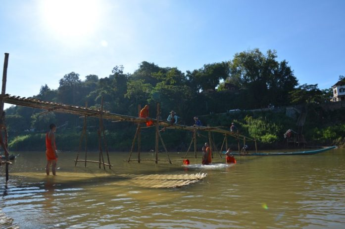 Monks helping build the bamboo bridge across the Nam Khan River, Luang Prabang, Laos