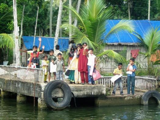 People waving from pier at Kerala India