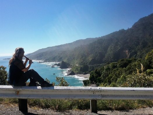 Woman playing flute overlooking seacliffs